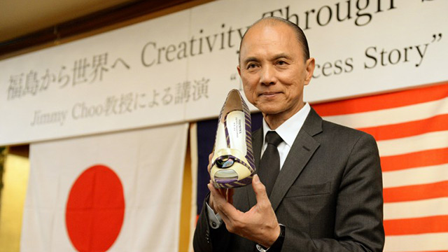 "Malaysian designer Jimmy Choo holds his one-off set of shoes using materials of Japan's Fukushima area during his lecture ""Creativity Thugh Skills"" in Fukushima city on April 18, 2014. World famous designer Jimmy Choo unveiled six pairs of shoes using materials and techniques native to Japan's Fukushima area, in a bid to boost the profile of artisans there struggling in the aftermath of the tsunami-sparked nuclear disaster. AFP PHOTO / TOSHIFUMI KITAMURA"